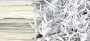 stacks of paper next to a pile of paper shreds