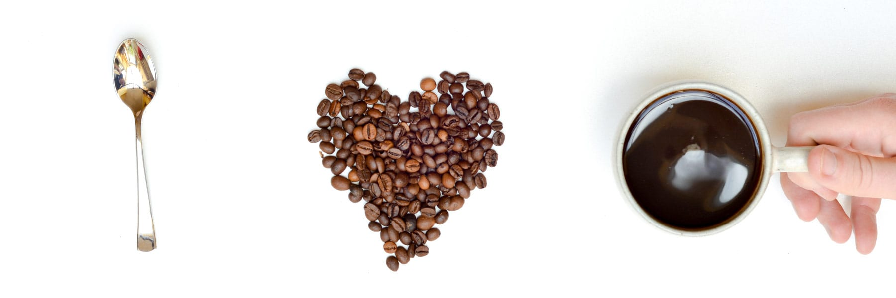 spoon, coffee beans layed out in heart, and cup of coffee