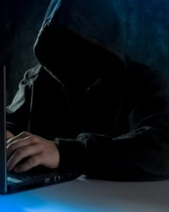 man in hood with face hidden in darkness at laptop