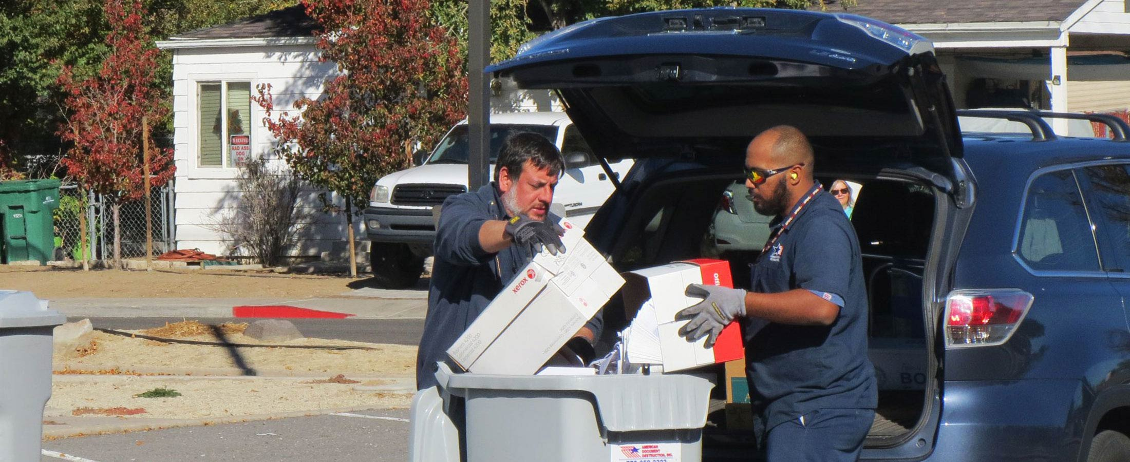 two workers emptying boxes of paper into shredding container