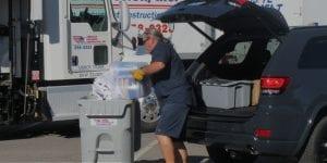 American Document Destruction worker emptying paper into shredding bin