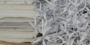 Stacks of paper next to pile of shreds