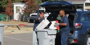 Two American Document Destruction workers emptying paper into shredding bin