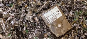 hard drive on top of a pile of hard drive destruction shreds